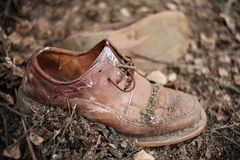 Dirty old pair of shoes covered in soil. Leather old shoes, covered in soil and dust Royalty Free Stock Photography