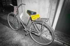 Dirty old pushbike leaning against wall in back street with brig. Dirty old pushbike leaning against wall in back street scene with bright yellow sign Do not Stock Photos