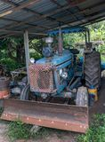 Dirty old tractor parked under a shed Stock Photo