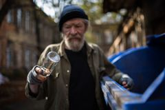 Dirty old tramp looking at empty bottle in his hand. Difficult life of homeless old man Royalty Free Stock Photography
