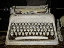 Dirty old typewriter on wooden shelf. royalty free stock images