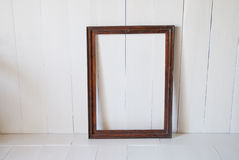 Dirty old vintage picture frame on the wall. White interior room stock images