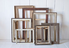 Dirty old vintage picture frames on the wall. White interior room royalty free stock image