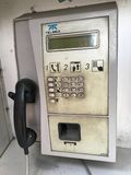 Dirty phone booth. Dirty old white phone booth in the street Royalty Free Stock Image