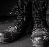 Dirty old work boots black and white stock images