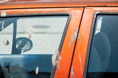 Dirty orange car covered with bird droppings or poop over the paint close up on the door and window.  stock image