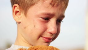 Dirty orphan boy close-up crying and petting a. Stuffed toy wipes the tears on the background of the  ruins stock footage