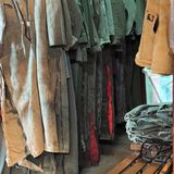 Dirty overalls hanging on rack in closet. Clean laundered jeans sit folded on bench, laundry hamper sits ready, and beige and olive green used filthy overalls royalty free stock image