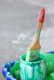 Dirty paint brush. Dirty brush in a bank with green paint Stock Photo