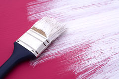 Dirty paintbrush with white paint on half-painted board Royalty Free Stock Photos