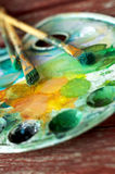 Dirty palette with acrylic paints and brushes Royalty Free Stock Photo
