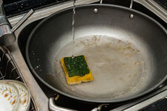 A dirty pan in the kitchen sink Stock Photos