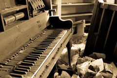 Dirty Piano With Trashed Furniture. Old dirty piano in a trashed room with garbage on the floor Royalty Free Stock Images