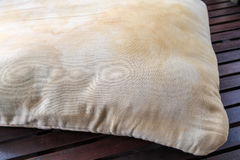Dirty pillow on wooden table. Stock Photos