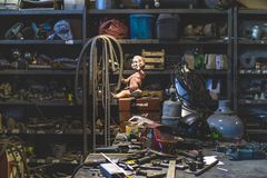 Dirty plastic baby doll posing inside of a metal shop royalty free stock photo