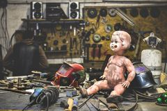 Dirty plastic baby doll posing inside of a metal work shop stock image