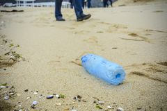 Dirty plastic bottle dropped on the beach. stock image