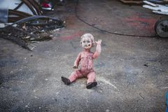 Dirty plastic naked baby doll sitting on the ground in front of a metal shop waving stock images