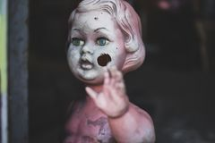 Dirty plastic naked baby doll standing by the door at the metal shop looking eerie and hunted weaving closeup stock photo