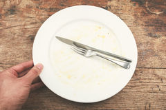 Dirty plate and cutlery. With a man's hand next to it Royalty Free Stock Photography