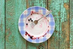 Dirty plate with fresh blueberries left on turquoise background Stock Photography