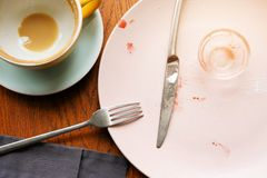A dirty plate with the remains of jam, dirty Cutlery and a mug of coffee in the restaurant, on a wooden table. Used dishes stock photo