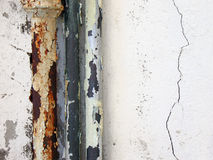 Dirty Plumbing. Old metal plumbing running up a white exterior wall royalty free stock photo