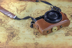Dirty pocket compact camera on a old world map Royalty Free Stock Photo