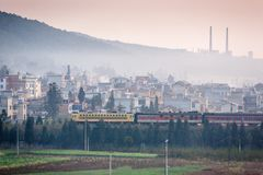 Dirty pollution. A train passes the old city of south Yunnan, China, land of coal. Coal mining with pipes on the mountain. Backgrounds, vegetable garden royalty free stock photography