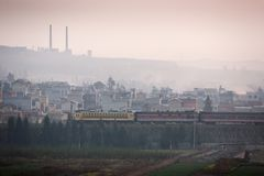 Dirty pollution. A train passes the old city of south Yunnan, China, land of coal. Coal mining with pipes on the mountain. Backgrounds, vegetable garden stock photography