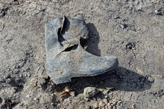 Dirty ragged rubber boot on the ground. Dirty ragged rubber boot in the sand on the ground Stock Image