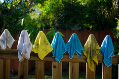 Dirty rags hanging on fence. A collection of colorful dirty microfiber  and  terrycloth rags or cleaning cloths on fence posts drying in the sun Stock Photos