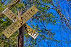Dirty rail road crossing sign on wooden post Royalty Free Stock Photos