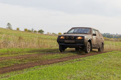 Dirty rally car racing on the road among fields. Royalty Free Stock Image