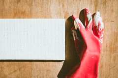 Dirty red glove on white and brown wooden Royalty Free Stock Photography