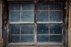 Dirty window in the old house shed. The dirty retro wooden window in the old house shed closeup Stock Images