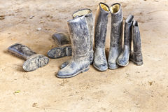 Dirty riding boots standing at muddy ground Royalty Free Stock Photography