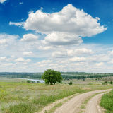 Dirty road and clouds over it Stock Photos