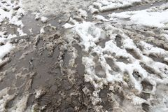 Dirty road with foot prints on wet soil and melting snow Royalty Free Stock Photography