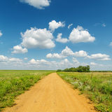 Dirty road in green fields under deep blue sky with clouds Stock Images