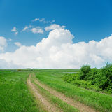 Dirty road in green landscape and clouds Stock Image