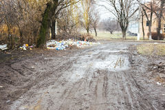 A dirty road and a pile of rubbish. Under a tree Royalty Free Stock Photos