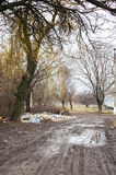 A dirty road and a pile of rubbish. Under a tree Stock Image