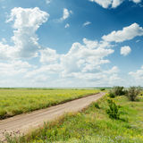 Dirty road to horizon and blue cloudy sky Royalty Free Stock Photography