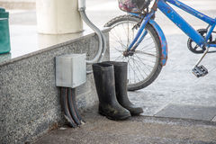 Dirty rubber boots beside old bicycle Stock Photo