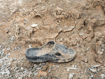 Dirty rubber shoe with the dry mud. Stock Image