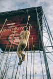 Dirty runner climbing rope in a test of obstacle race Stock Images