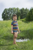 Dirty rural barefoot boy standing near a puddle. Royalty Free Stock Photos