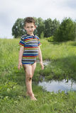 Dirty rural barefoot boy standing near a puddle. Royalty Free Stock Image