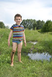 Dirty rural barefoot boy standing near a puddle. Royalty Free Stock Photography